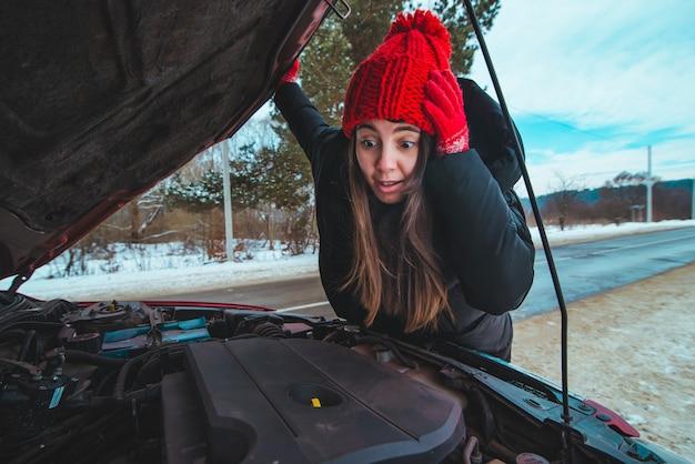 Женщина смотрит на концепцию дорожной помощи двигателя автомобиля зимний сезон