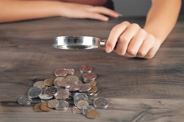 돋보기로 동전을 보는 여자