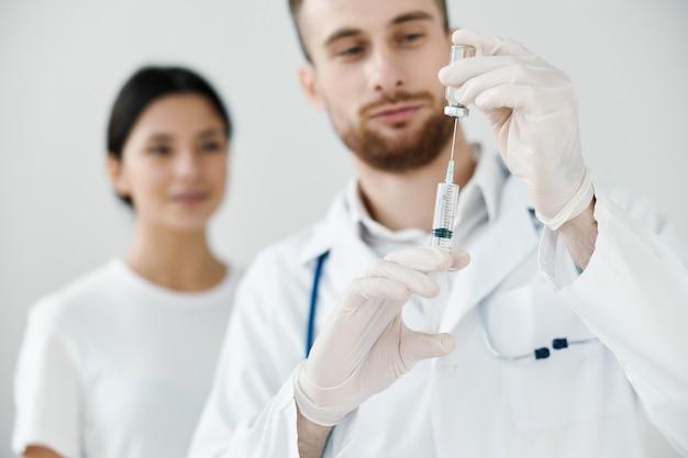 손 예방 접종 의료 장갑 청진기에 주사기와 의사를보고하는 여자. 고품질 사진