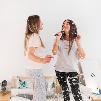 Woman looking at female friends singing with flying feathers in the bedroom