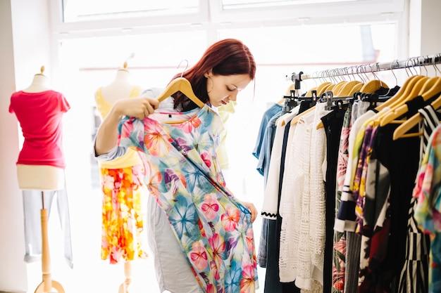 Женщина, глядя на цветочное платье
