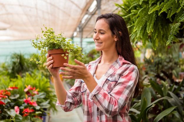 Женщина смотрит на цветочный горшок в теплице