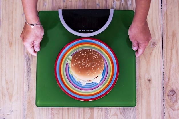Женщина смотрит на гамбургер на зеленом балансе веса - концепция здоровья и здорового образа жизни для плана похудания диеты - вертикальный вид