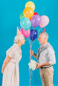 Woman looking at her husband holding colorful balloons and birthday gift on blue backdrop