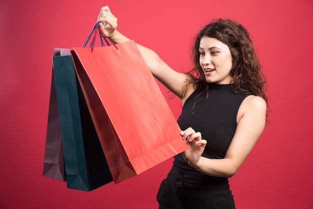 Женщина смотрит на свою новую одежду покупки на красном фоне