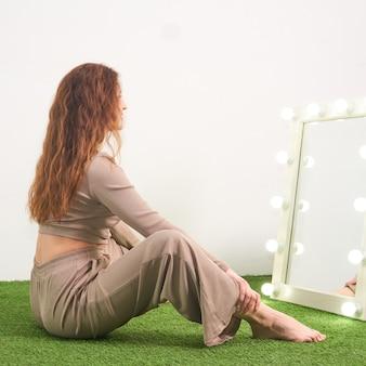 스튜디오 바닥에 앉아 있는 탈의실용 조명 거울에 비친 자신의 모습을 바라보는 여성