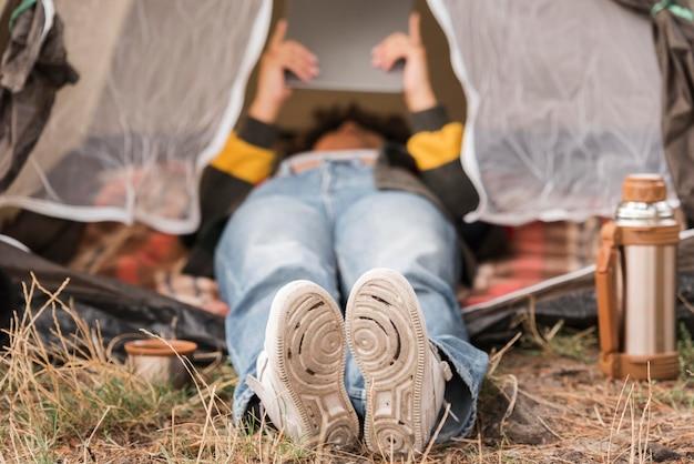 Женщина смотрит на свой планшет в палатке во время кемпинга