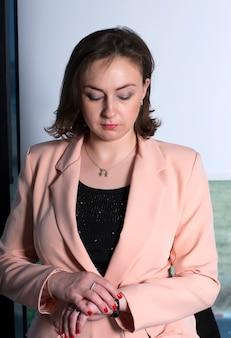彼女の時計を見ている女性。ビジネスの女性は、オフィスの時計で時間を見る