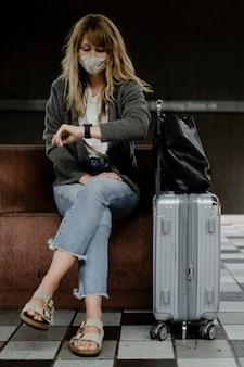 코로나바이러스 전염병 동안 기차를 기다리는 동안 시계를 보고 있는 여성