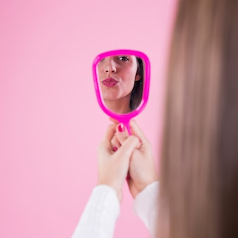 Woman looking at herself in mirror and blowing kiss