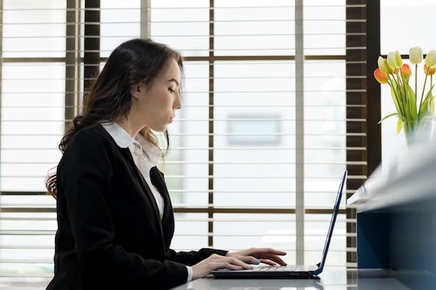 新しいプロジェクトを考えて、ラップトップコンピューターを見て女性
