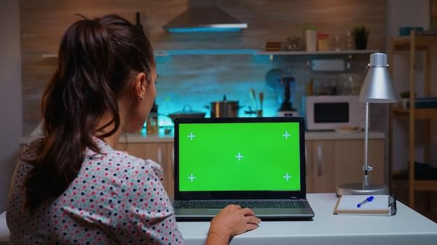 집 부엌에서 밤 시간에 녹색 모형이 있는 노트북을 보고 있는 여자. 야간 근무 시간 동안 녹색 화면, 크로마 키가 있는 데스크탑 모니터 디스플레이를 보는 프리랜서.