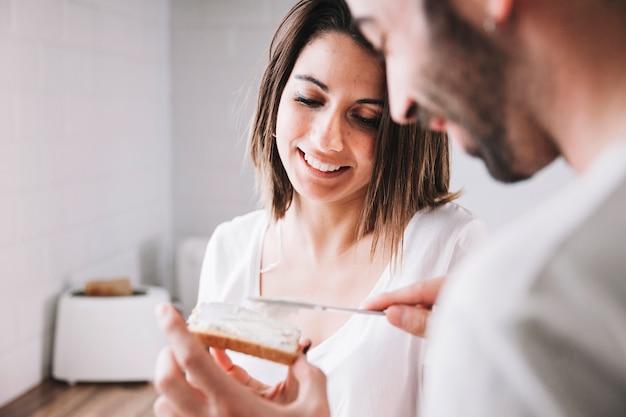 トーストを作る男を見ている女性