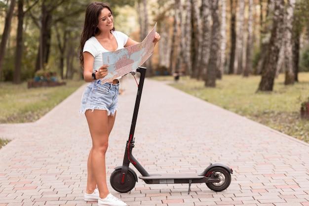 電動スクーターの横にある地図を見ている女性