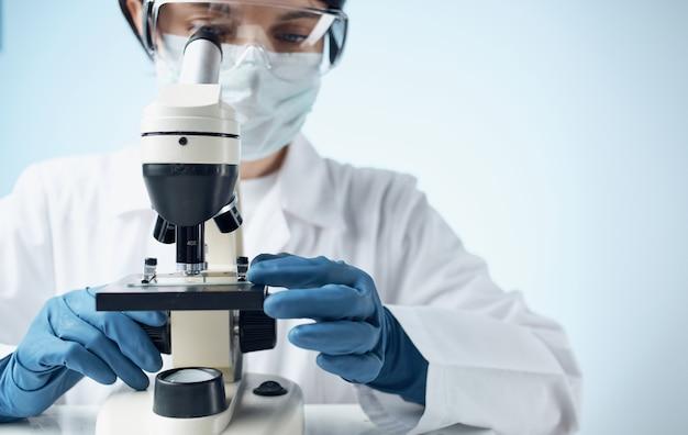 Женщина смотрит в микроскоп лабораторные исследования микроорганизмов бактерий