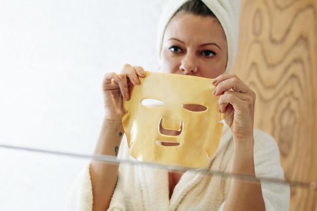 주름을 없애기 위해 얼굴에 금색 젤 시트 마스크를 적용할 때 거울을 보는 여성