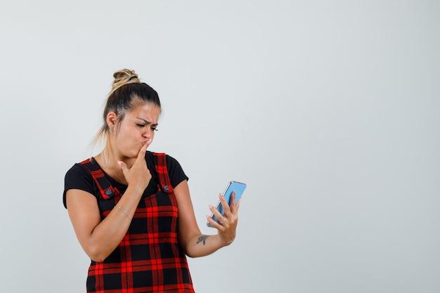 Женщина смотрит на мобильный телефон в платье-сарафане и нерешительно смотрит, вид спереди.