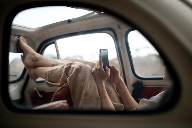 Женщина смотрит на мобильный телефон в ретро-автомобиле