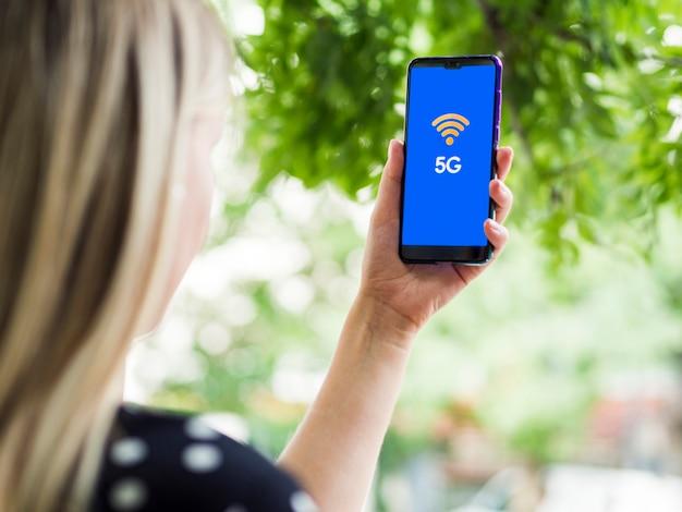 画面上の5 gで携帯電話の画面を見ている女性