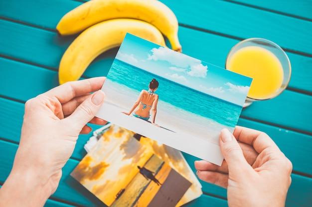 Женщина смотрит фотографии в руках. вид сверху.