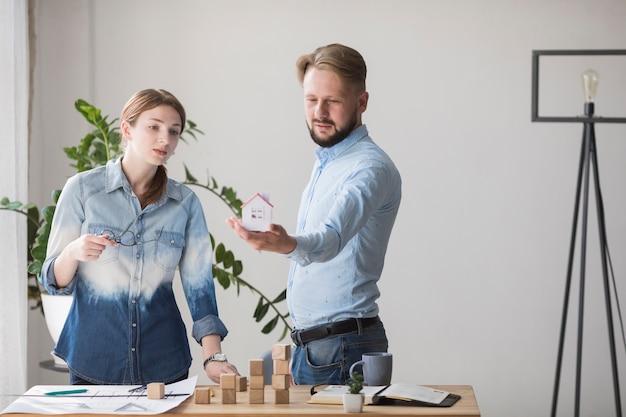Женщина, глядя на модель небольшого дома, ее коллега на рабочем месте