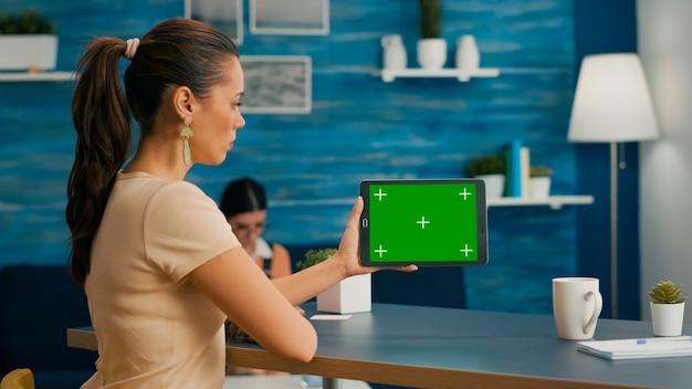 인터넷 검색 라이프스타일 아이디어를 탐색하는 녹색 화면 크로마 키 디스플레이가 있는 태블릿 컴퓨터를 보고 있는 여성. 거실의 책상 사무실에 격리된 장치를 사용하는 프리랜서