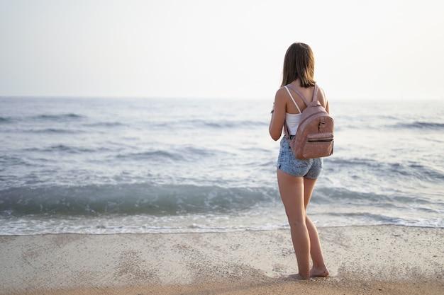 Женщина смотрит на море с берега пляжа, горизонтально, копией пространства