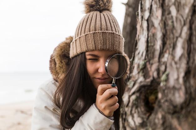 Женщина, глядя на дерево коры через увеличительное стекло