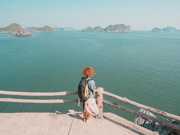 Женщина смотря уникальный взгляд залива halong, вьетнама. турист на набережной на острове кат ба среди скалистых вершин бухты халонг в море