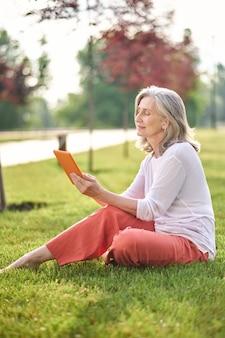 Женщина, внимательно глядя на планшет, сидя на лужайке