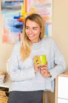 Женщина смотрит в сторону и держит чашку кофе