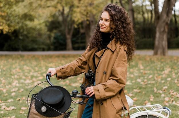 Женщина смотрит в сторону и держит велосипед