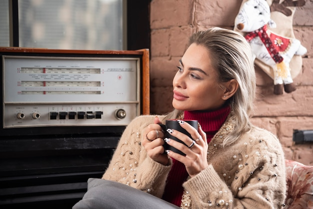 A woman looking away and drinking coffee