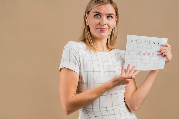 Woman looking away and showing her period calendar