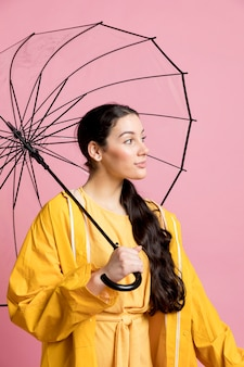 Woman looking away while holding an umbrella