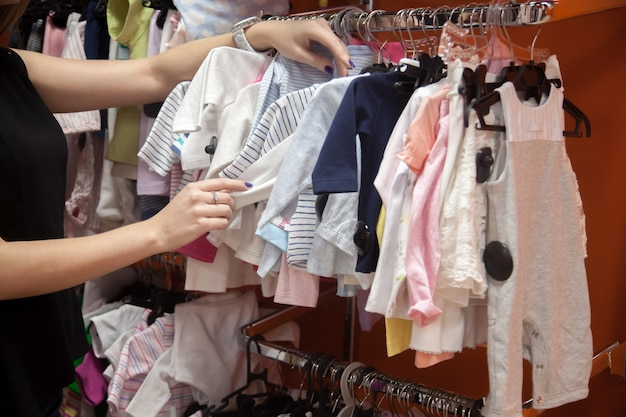 Woman looking at baby clothes