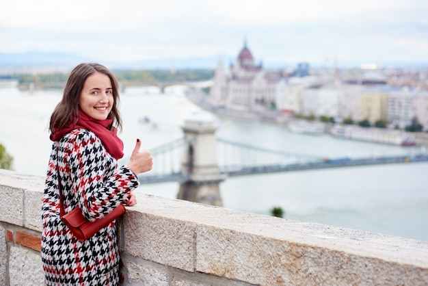 Woman looking back at the camera with smile and showing thumb up gesture of good class, against beautiful view of the hungarian parliament and the chain bridge in budapest, hungary.