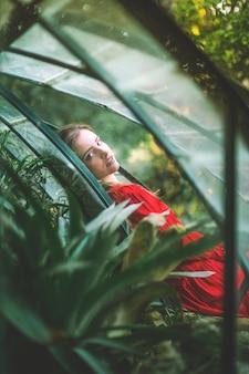 Woman looking at camera and blurred foliage