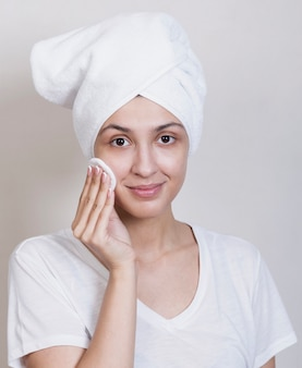 Woman looking at camera cleaning face