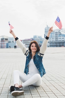 Woman looking at camera sitting on square and waving american flags in hands