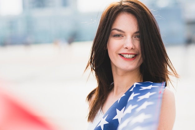 Woman looking at camera and smiling waving with stars of american flag