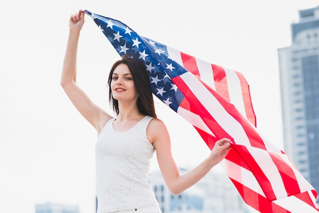 Woman looking at camera and waving american flag