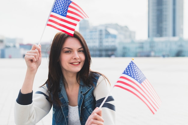 Woman looking at camera and waving american flags in hands