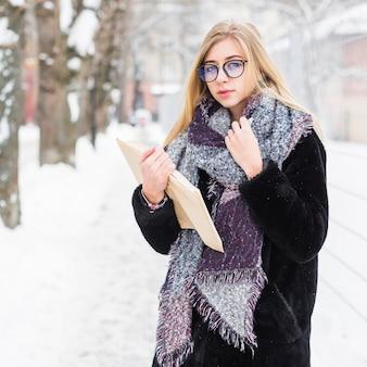 Woman looking at camera while enjoying reading on street