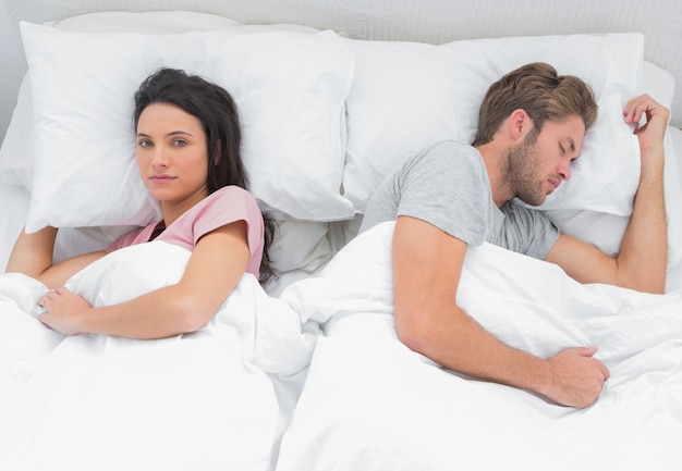 Woman looking at camera while her husband is sleeping