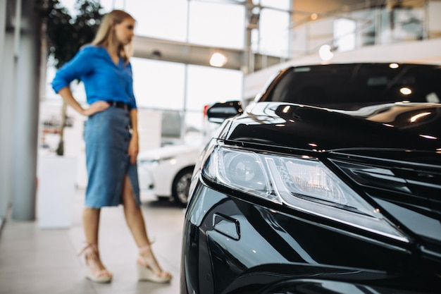 Woman looking at a car in a car showroom