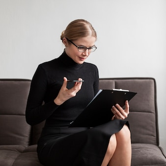 Woman looking at clipboard and holding mobile