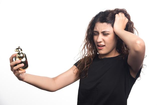 Donna che guarda l'orologio e tenendo la testa su sfondo bianco
