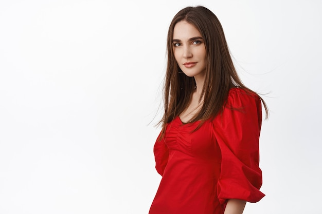 女性、自信を持って生意気な顔をして、情熱的な赤いフラメンコドレスを着て、白の上に立っています。