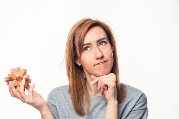 Woman looking confused with wooden puzzle.